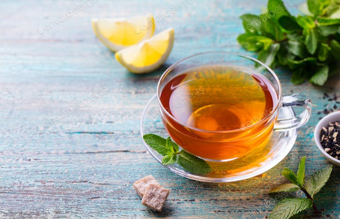 Tea Cup with Mint Leaves and Lemon. Wooden Background. Copy Space.