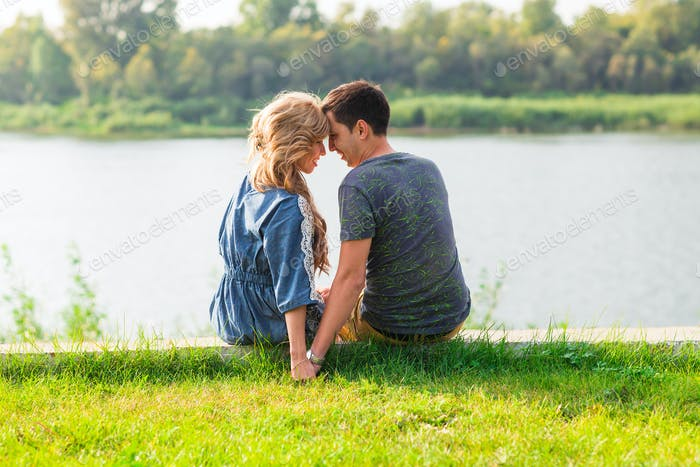 Young love couple sitting on the river bank in summer