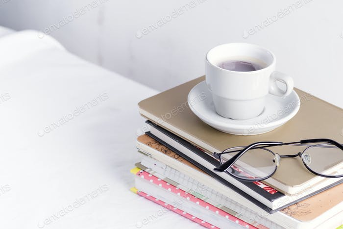 Stack of different books and notepads with woman's glasses and coffee cup on the top on a white