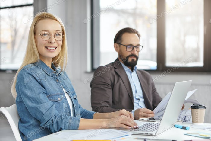 Female and male economists work with documents and modern technologies, sit over modern office inter