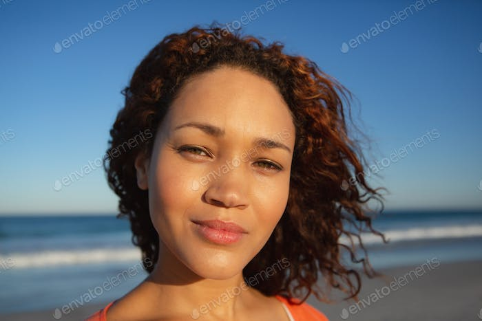 Close-up of beautiful mixed race woman looking at camera on beach in the sunshine