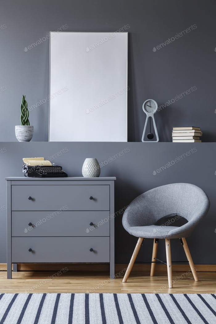 Grey armchair next to cabinet in apartment interior with mockup