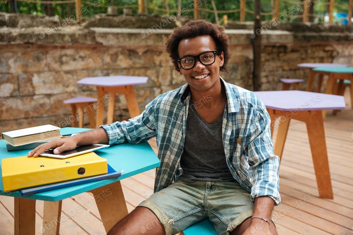 Cheerful young man sitting and smiling in outdoor cafe