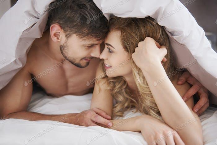 Paar verliebt unter der Bettdecke