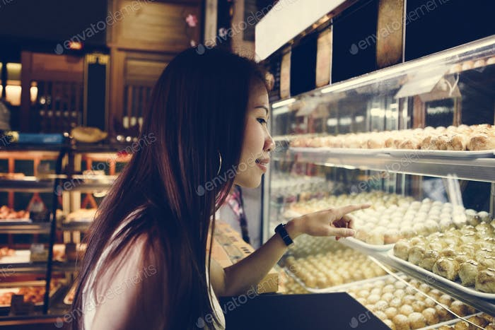 Asian girl pointing at Chinese pastries
