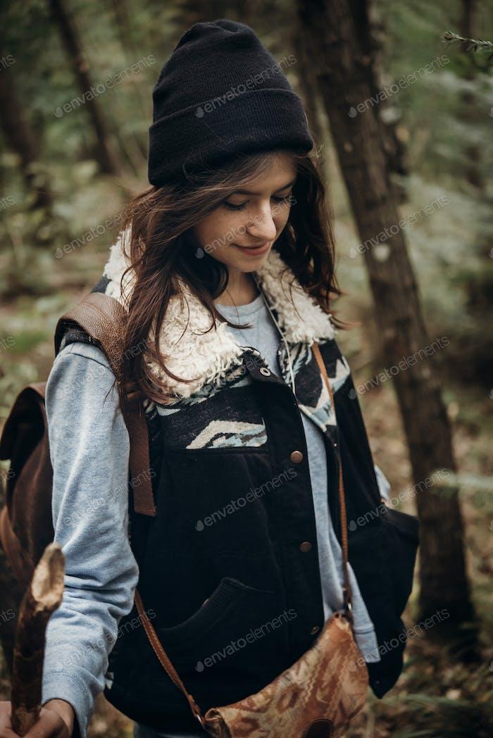 beautiful hipster traveler smiling, walking in woods