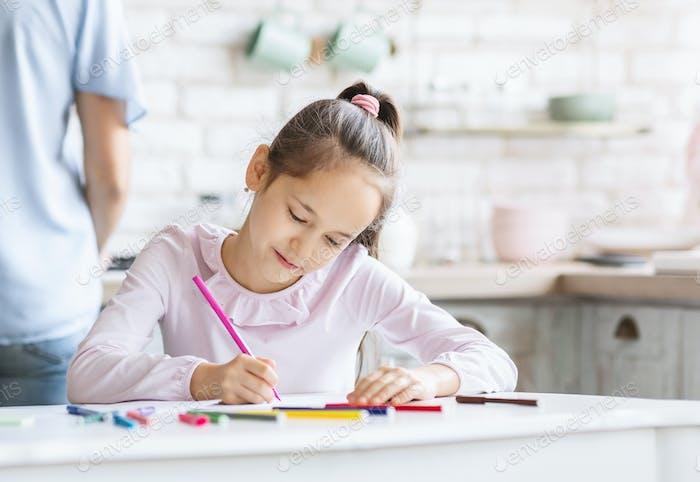 Portrait of beautiful little girl drawing in kitchen
