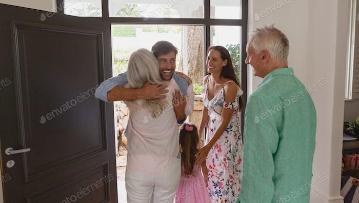 Happy active senior Caucasian woman embracing  Caucasian man at door in a comfortable home