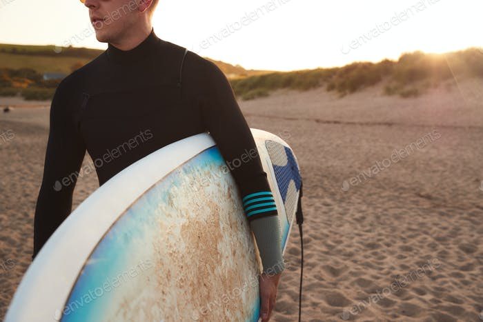 Close Up Of Young Man Wearing Wetsuit Enjoying Surfing Staycation On Beach As Sun Sets