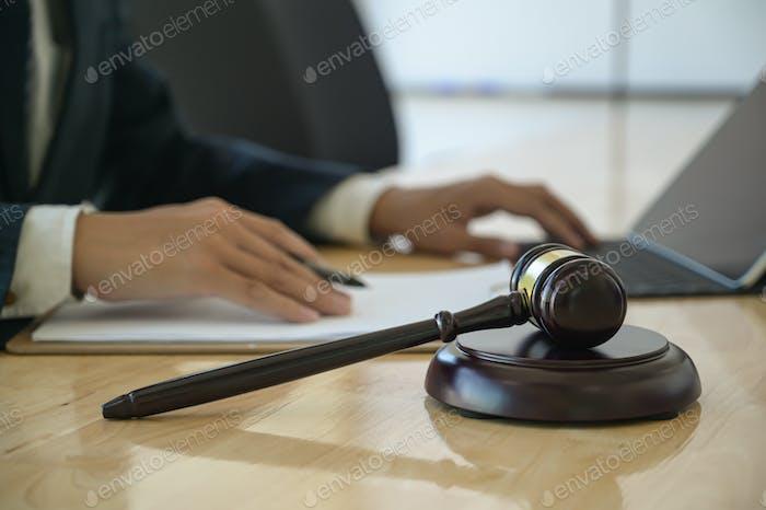 Konzept der Gerechtigkeit, Hammer auf dem Schreibtisch mit Anwalt platziert verwendet einen Laptop hinter sitzen.