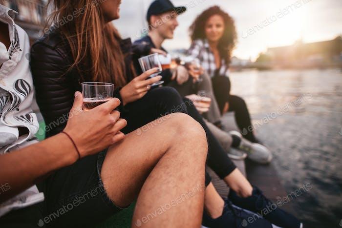 Gruppe von Menschen, die auf dem Pier sitzen und trinken