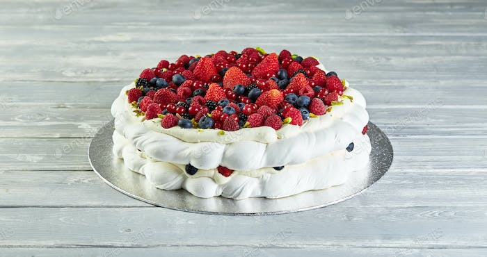 Meringue pavlova wreath cakes with whipped cream and fresh berries,