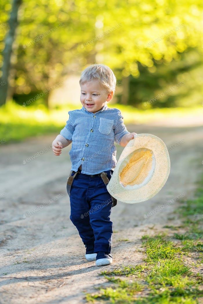Kleinkind Kind im Freien Ländliche Szene mit einem Jahr alten Baby Jungen mit Strohhut