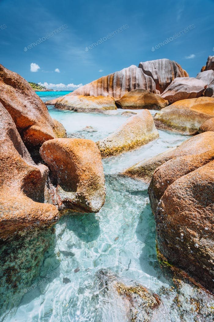 Bizarre shaped rocks in blue ocean water on Anse Cocos beach, La Digue island, Seychelles