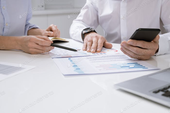 Hands of contemporary economists discussing financial chart on paper
