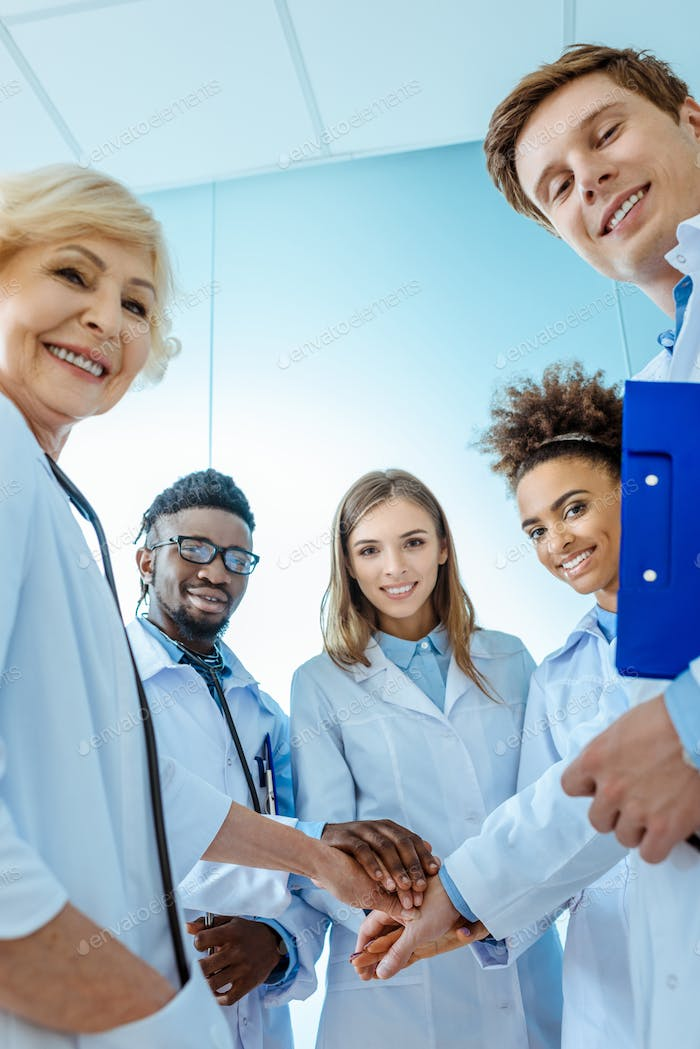 A multiracial group of medical interns in labcoats with clipboards and stethoscopes standing in a
