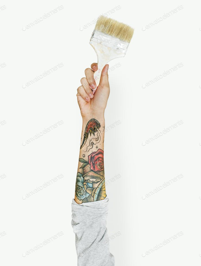 Hand with tattoo holding a paint brush
