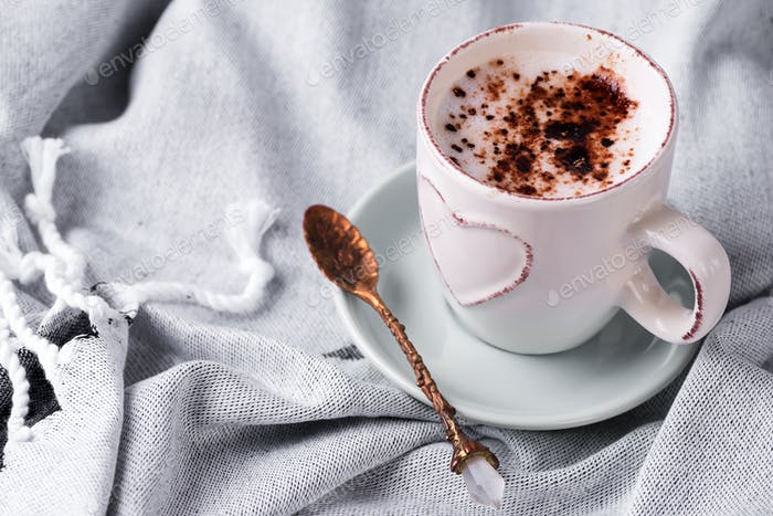 Having a cup of coffee with chocolate on blanket in bed
