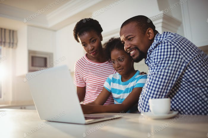 Parents and daughter using laptop in kitchen
