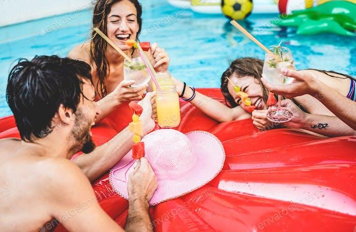 Glückliche Freunde trinken Cocktails und essen tropische Früchte auf Schwimmbadparty