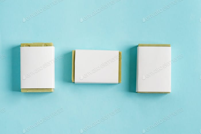Three soap wrap box mock-up package with bar olive soap isolated on blue background
