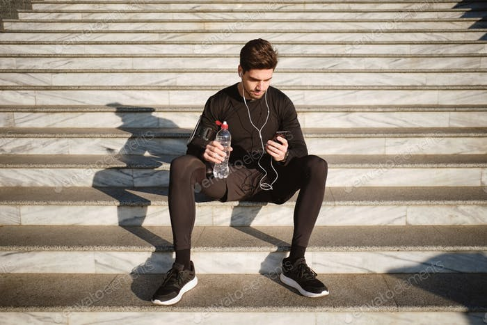 Young attractive smiling sporty man sitting on stairs using cellphone after workout outdoor