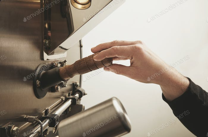 La mano de trabajo está lista para tomar la sonda de granos de café tostados