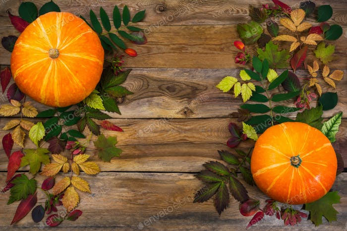 Thanksgiving decoration with leaves and pumpkin on the old table