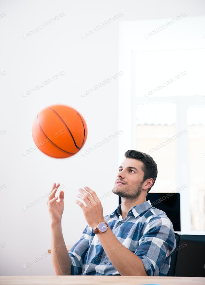 Happy businessman throwing ball in office
