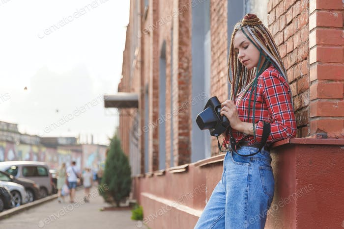 Hipster young photographer girl on the street with retro camera