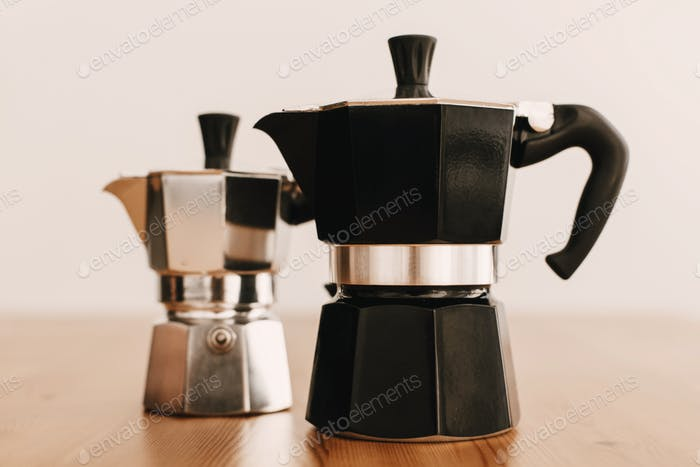 Steel and black geyser coffee makers on wooden table
