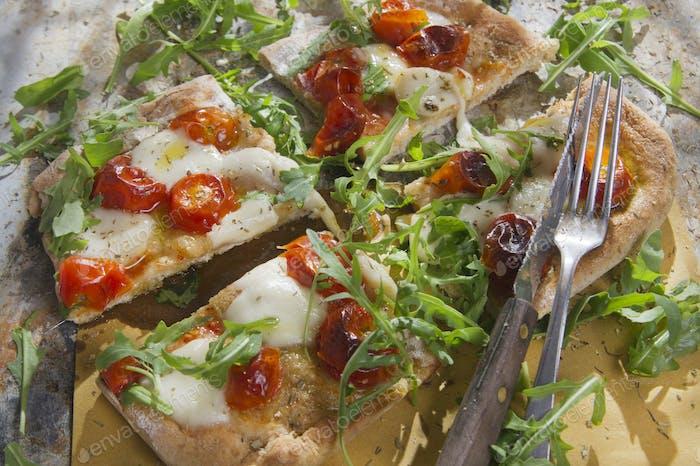 Pizza con tomate y rúcula