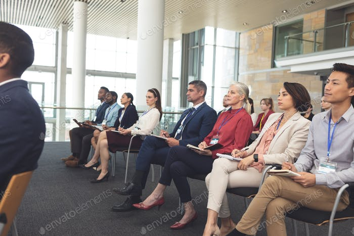 Side view of diverse well dressed business people attending a business seminar in office building