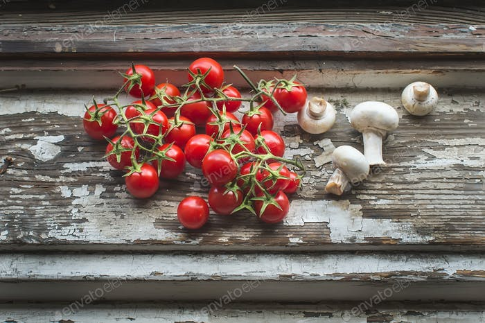 Cherry-tomatoes and field mushrooms over a old painted wood surf