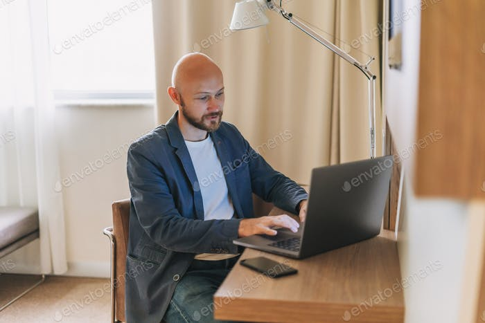 Adult bald bearded man in blue jacket with working on laptop in hotel room