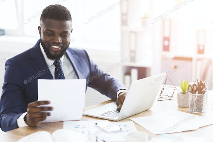 Satisfied black businessman checking documents, sitting in modern office