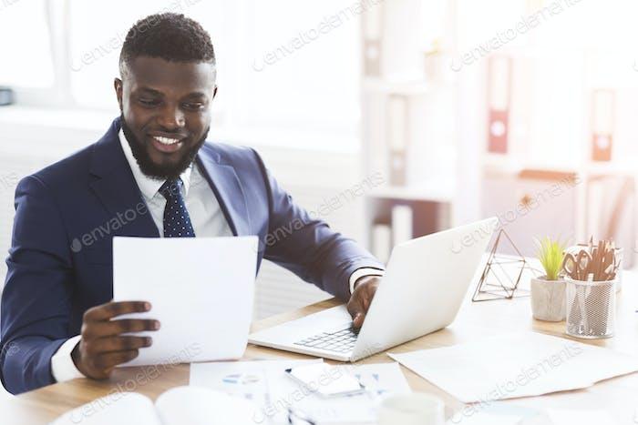 Zufriedene schwarze Geschäftsmann Überprüfung von Dokumenten, sitzen im modernen Büro