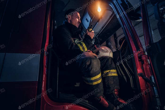 Fireman in a protective uniform sitting in the fire truck and talking on the radio