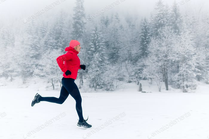 Girl running on snow in winter mountains