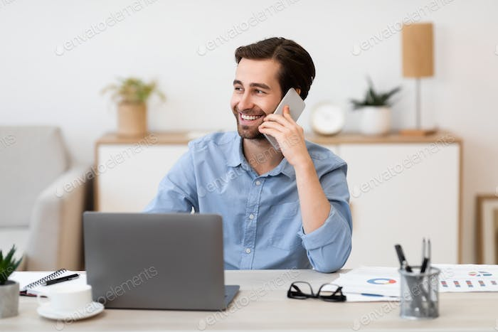 Cheerful Businessman Talking On Phone In Office Sitting At Workplace