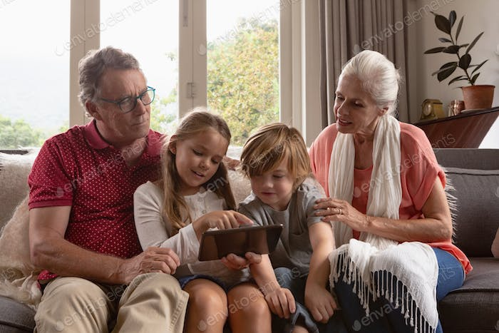 Front view of multi-generation Caucasian family using digital tablet on sofa in a comfortable home