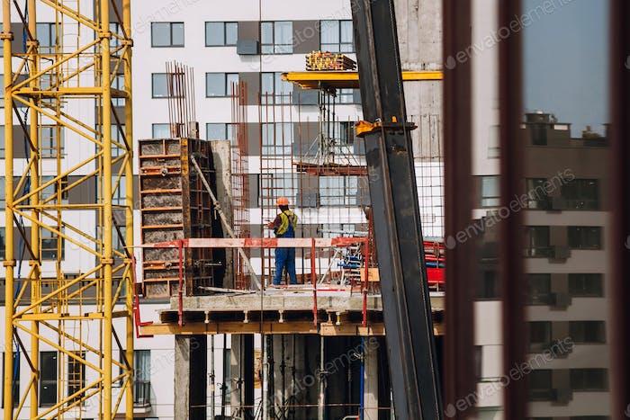 Trabajadores ingenieros que trabajan en el sitio de construcción y grúas en el fondo de los nuevos rascacielos de construcción