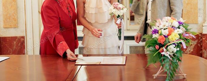 stilvollen Luxus Bräutigam und Braut im Vintage-Kleid Unterzeichnung Ehe offizielles Dokument