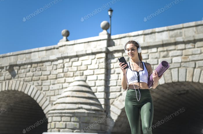 happu fit woman in the park walking with mat to do yoga , pilates and train listening music