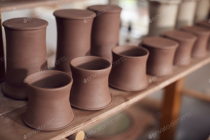 Clay Pots On Shelf Waiting For Decoration In Ceramics Studio