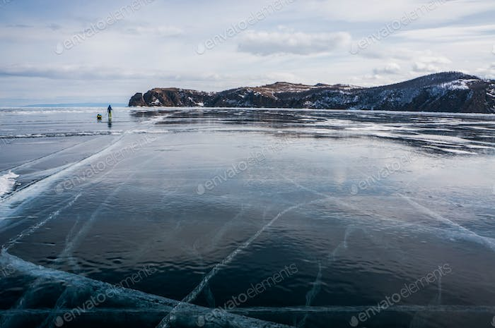 scenic view of frozen river with snowy mountains in winter, Russia, Lake Baikal, march 2020