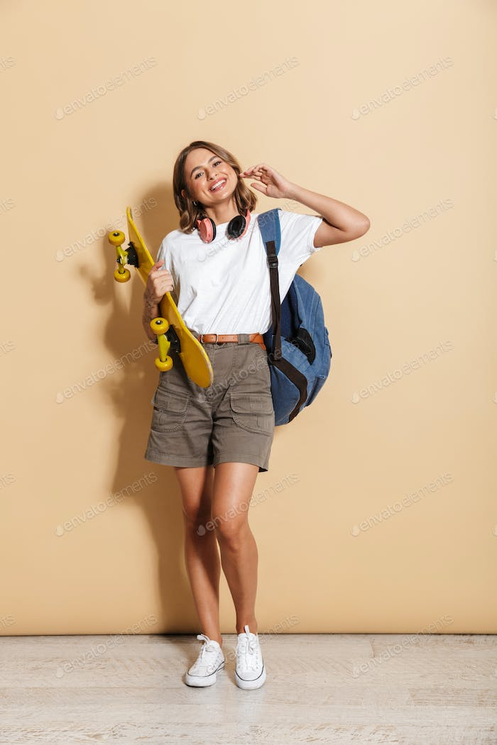 Portrait of a smiling schoolgirl carrying backpack standing