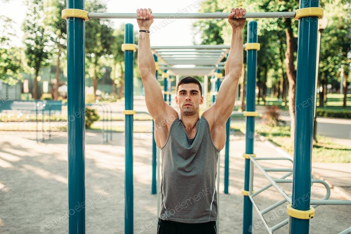 Athlete doing exercise on horizontal bar outdoor