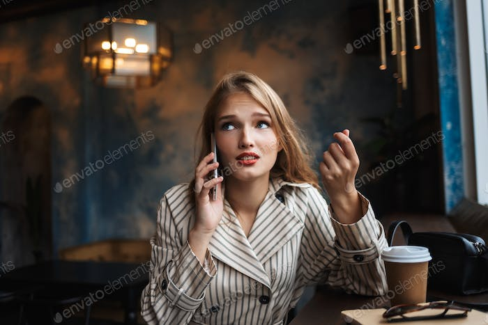 Young woman in striped trench coat  talking on cellphone thought