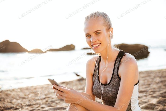 Lächelnd blonde Sport Frau mit Ohrhörer sitzen am Strand